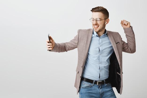 Feliz empresário dançando alegre com smartphone, ouvindo música em fones de ouvido sem fio