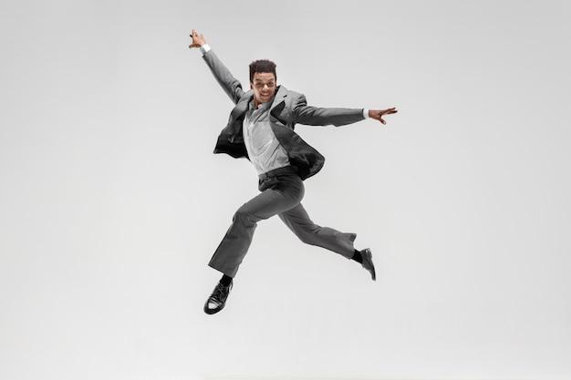 Feliz empresário dançando em movimento isolado no fundo branco do estúdio. flexibilidade e graça nos negócios. conceito de emoções humanas. escritório, sucesso, profissional, felicidade, conceitos de expressão