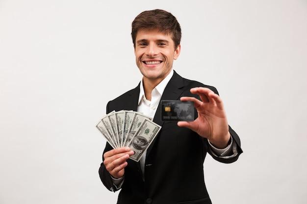 Feliz empresário em pé isolado segurando dinheiro e cartão de crédito.