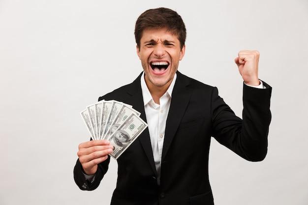 Feliz empresário em pé isolado segurando dinheiro faz gesto de vencedor.