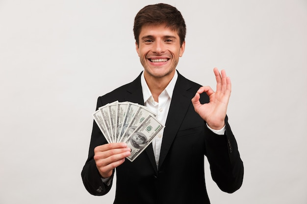 Feliz empresário em pé isolado segurando dinheiro faz o gesto certo.
