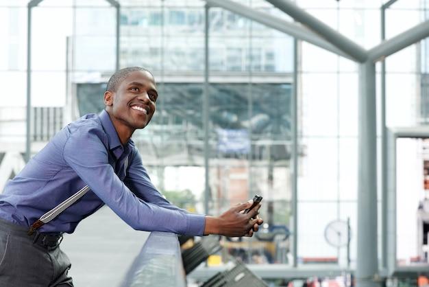 Feliz empresário em pé no edifício com telefone móvel
