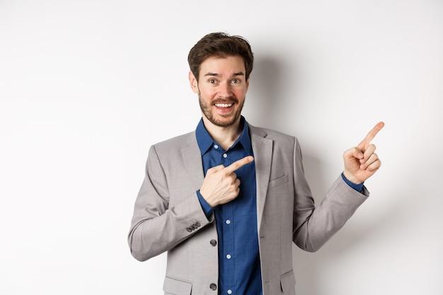 Feliz empresário em terno apontando os dedos certos e sorrindo animado, mostrando uma oferta especial, de pé sobre fundo branco.