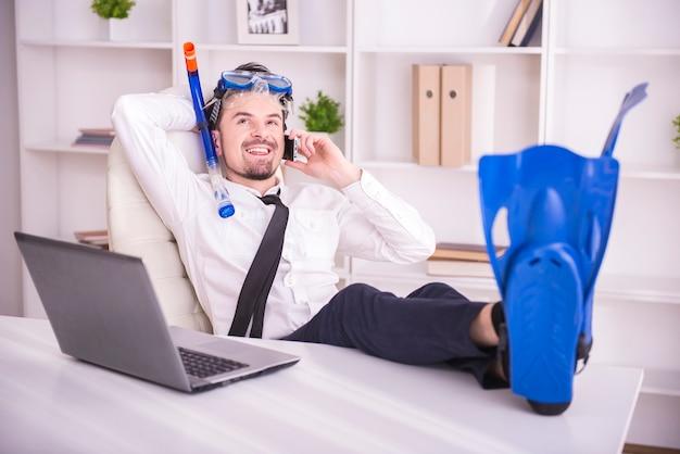 Feliz empresário está trabalhando no escritório está usando nas barbatanas.