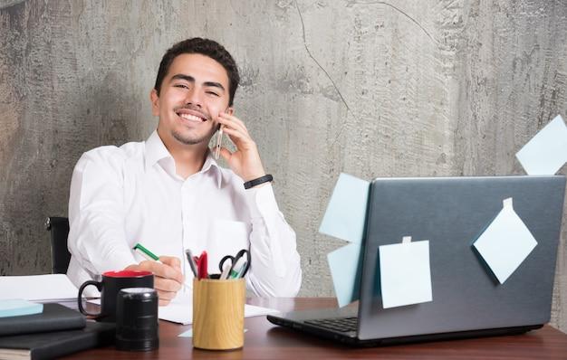 Feliz empresário falando sobre negócios e tomando notas na mesa do escritório.