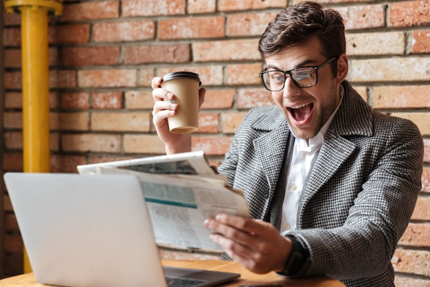 Feliz empresário gritando de óculos, sentado junto à mesa