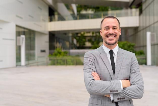 Feliz empresário hispânico careca e barbudo sorrindo com os braços cruzados ao ar livre da cidade