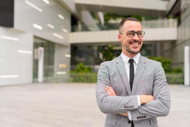 Feliz empresário hispânico de barba careca pensando com os braços cruzados ao ar livre da cidade