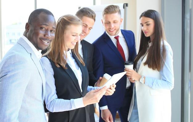 Feliz empresário inteligente com companheiros de equipe discutindo em segundo plano