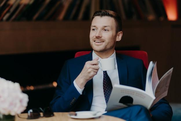 Feliz empresário lê revista popular na cafeteria, bebe café aromático