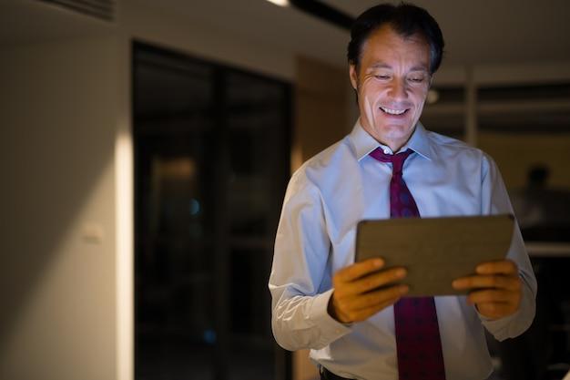 Feliz empresário maduro no escritório à noite usando tablet digital