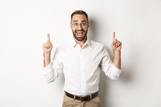 Feliz empresário masculino com roupas de negócios, apontando o dedo para cima e mostrando a oferta promocional, em pé
