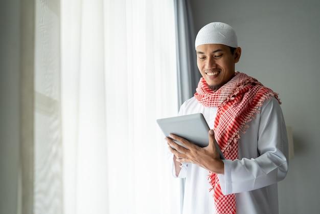 Feliz empresário muçulmano sorrindo enquanto usa o tablet pc perto da janela
