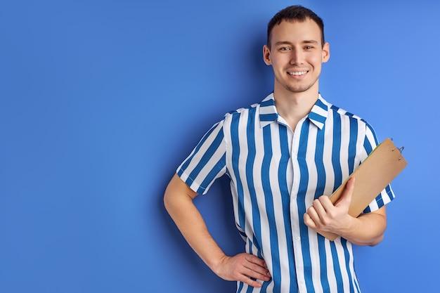 Feliz empresário ou empresário com prancheta isolada em fundo azul, retrato de um cara bonito em camisa azul listrada, olhando para a câmera com um sorriso encantador