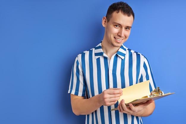 Feliz empresário ou empresário com prancheta isolada em fundo azul, retrato de um cara bonito em camisa azul listrada