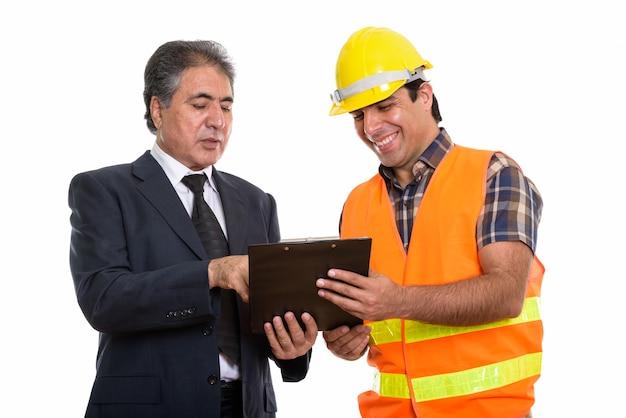 Feliz empresário persa sênior e jovem trabalhador da construção civil
