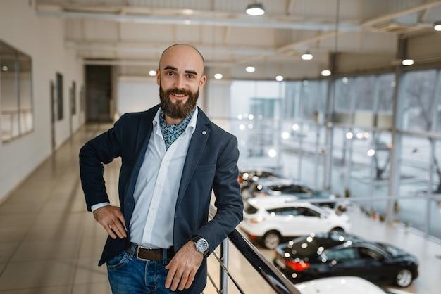 Feliz empresário posa na concessionária de automóveis. cliente em showroom de veículos novos, homem comprando automóvel, concessionária de automóveis