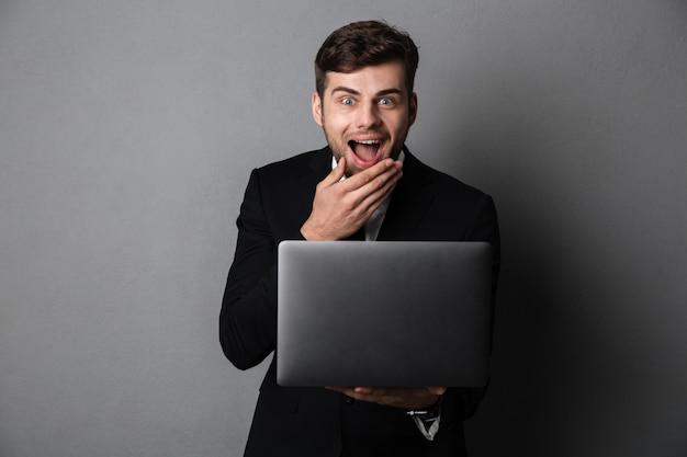 Feliz empresário saiu cobrindo a boca enquanto segura o laptop