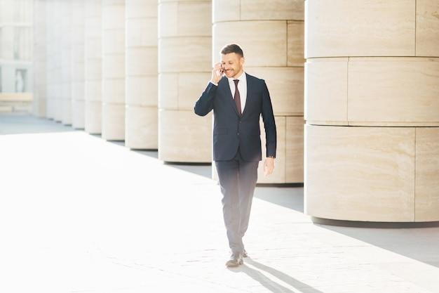 Feliz empresário satisfeito faz conversa telefônica