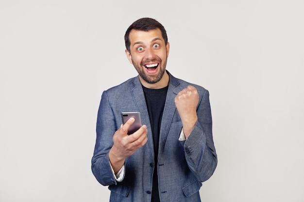 Feliz empresário segurando um smartphone e comemorando sua vitória e sucesso está muito animado, encorajando emoções.