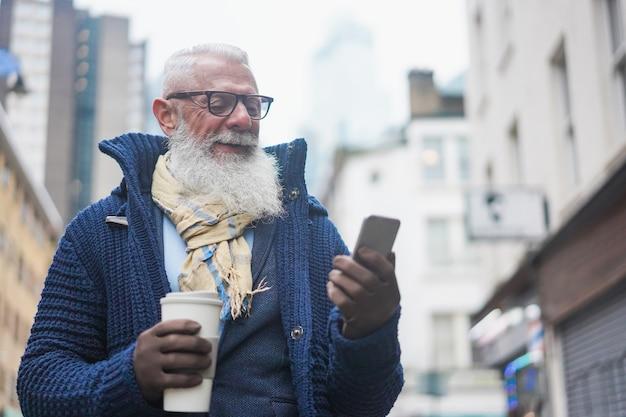 Feliz empresário sênior hippie usando telefone celular enquanto bebe café no dia de inverno