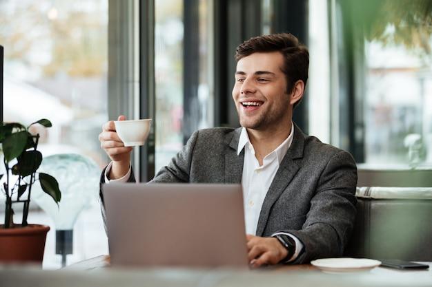 Feliz empresário sentado à mesa no café com o computador portátil, mantendo a xícara de café e olhando para longe