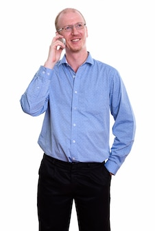 Feliz empresário sorrindo enquanto fala no celular e pensa