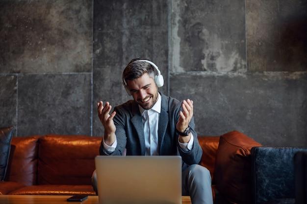 Feliz empresário usando fones de ouvido e sentado no corredor de um hotel e tendo uma chamada em conferência com parceiros de negócios. eles têm um acordo. telecomunicações, reunião online