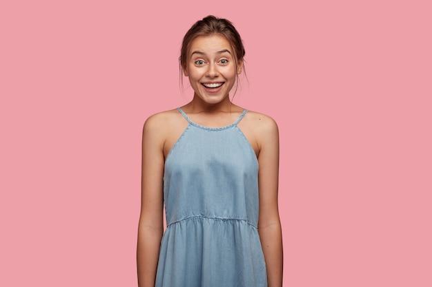 Feliz encantada jovem caucasiana sorri com alegria, parece com os olhos cheios de felicidade, vestida com roupa da moda, alegra-se com o resto do verão, modelos contra a parede rosa. conceito de emoções