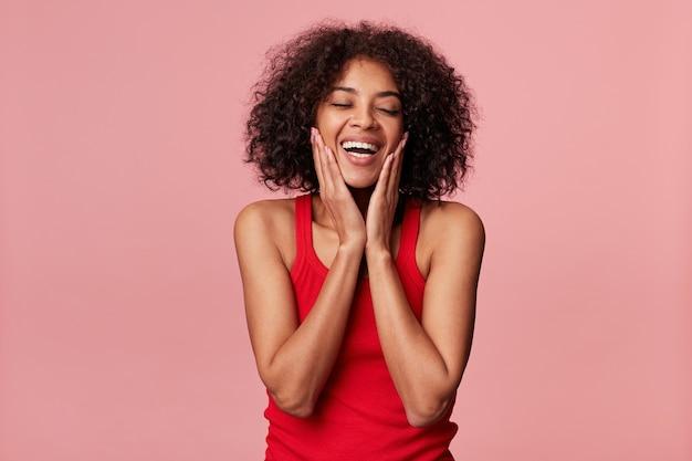 Feliz encantadora garota afro-americana com penteado afro fecha os olhos de prazer, toca o rosto com as palmas das mãos, ri, se alegra com a pele macia, vestindo camiseta vermelha, isolada