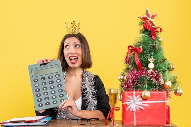 Feliz encantadora senhora de terno com coroa segurando calculadora no escritório em amarelo isolado
