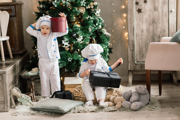 Feliz engraçado dois irmãos fazem biscoitos de natal perto da árvore de natal.