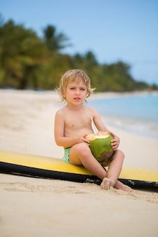 Feliz engraçado pré-escolar garoto menino bebendo suco de coco na praia do oceano.