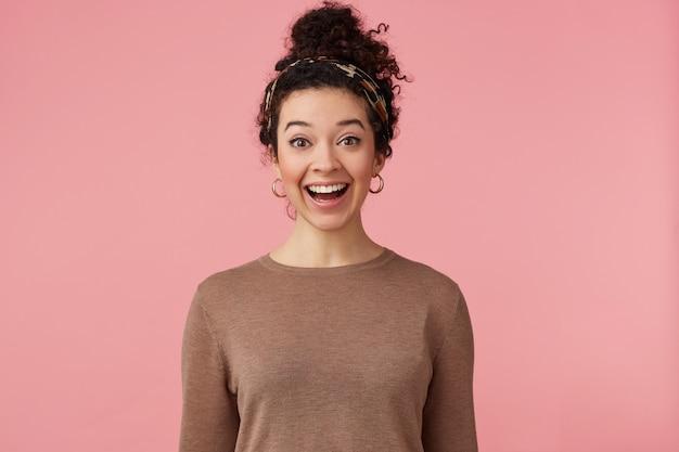 Feliz espantada jovem bonita com cabelo escuro encaracolado, ouviu as notícias legais, amplamente sorrindo e olhando para a câmera com os olhos bem abertos isolados sobre fundo rosa.