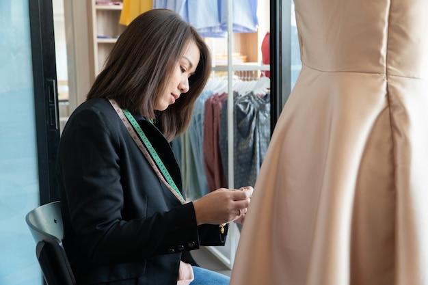 Feliz estilista de moda jovem asiática está testando a finalização de um vestido