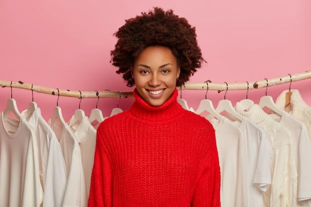 Feliz estilista feminina de pele escura com penteado afro, sorri amplamente, usa um suéter vermelho tricotado, fica perto de uma prateleira com cabides.
