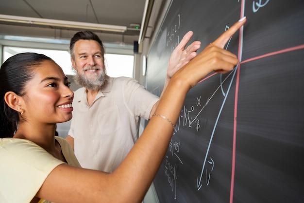 Feliz estudante adolescente do ensino médio mostra a solução do problema de matemática do professor apontando com o dedo para resultar. conceito de educação.