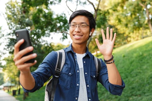 Feliz estudante asiático do sexo masculino em óculos fazendo selfie no smartphone e acenando para a câmera enquanto está no parque