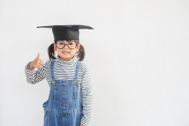 Feliz estudante asiático se formando com chapéu de formatura