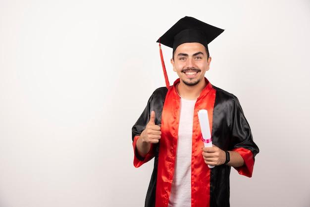Feliz estudante do sexo masculino com diploma fazendo polegares para cima em branco.