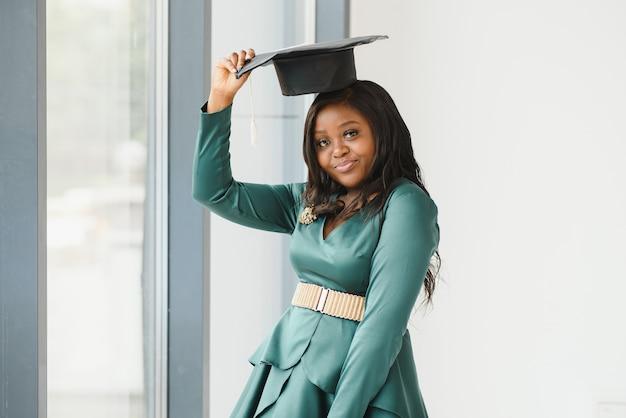 Feliz estudante universitário indiano em vestido de formatura e boné, segurando o certificado do diploma. retrato de mestiços indiano asiático e africano.