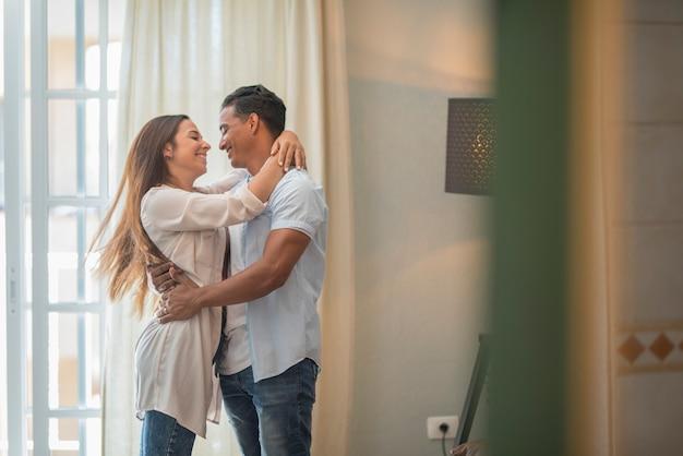 Feliz etnia mestiça em casa sente-se animado dançando e segurando-se com diversão, sorrindo e cheio de alegria casal aprecia a comemoração do aniversário dançando e dançando juntos no amor e no relacionamento