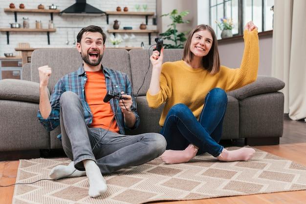 Feliz, excitado, par jovem, alegrando, após, ganhar, jogando videogame