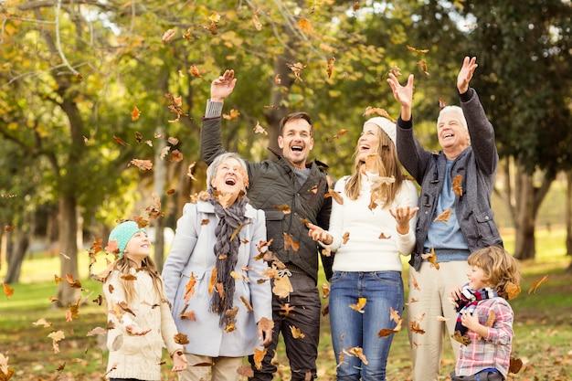 Feliz família alargada jogando folhas ao redor