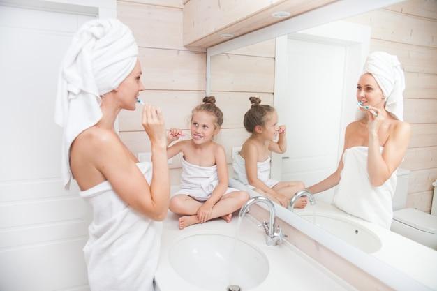 Feliz família amorosa mãe e filha com toalhas de escovar os dentes no banheiro branco.