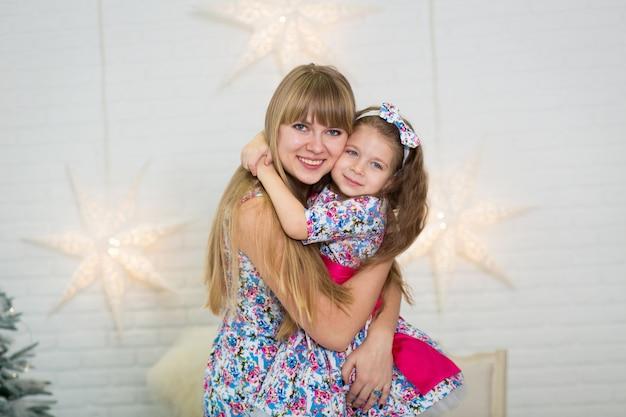 Feliz família amorosa. mãe e filha filha criança nos mesmos vestidos brincando e abraçando.
