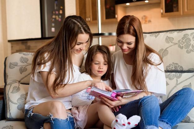 Feliz família amorosa. mãe muito jovem e sua irmã lendo um livro para sua filha.