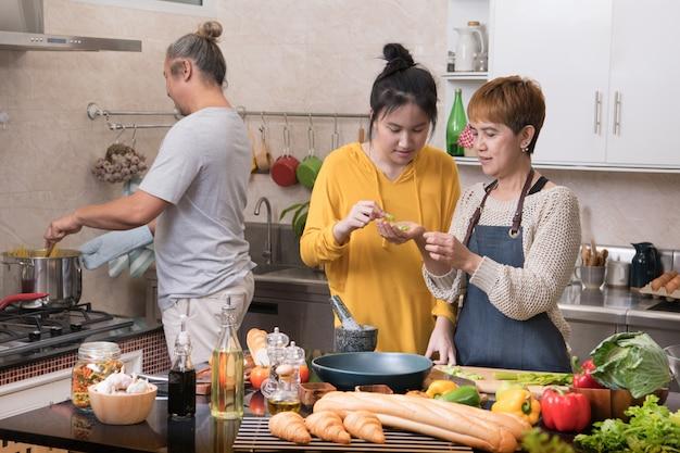 Feliz família asiática da mãe pai e filha cozinhando na cozinha, fazendo comida saudável, se divertindo juntos