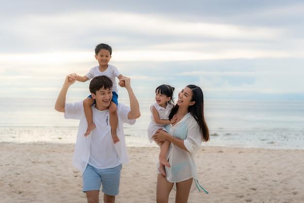 Feliz família asiática de férias na praia