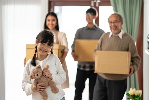 Feliz família asiática de várias gerações segurando uma caixa de papelão e se mudando para uma nova casa